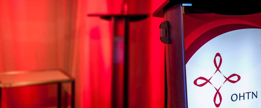 A podium with the OHTN logo on it stands before a curtain, chair, and table in dramatic red lighting.