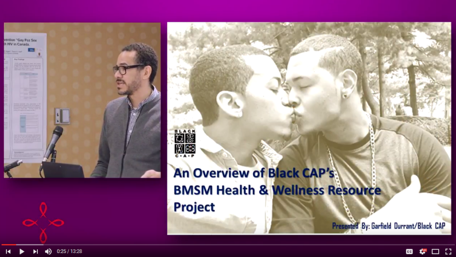 Presentor Garfield Durrant talking about the BMSM project next to an image of two Black men kissing