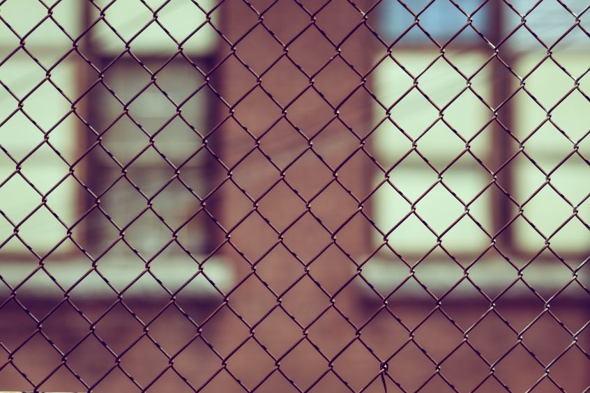 Looking at a building through a chain link fence