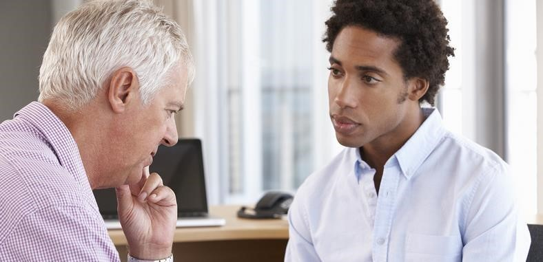 Therapist talking to an older gay man in an office setting
