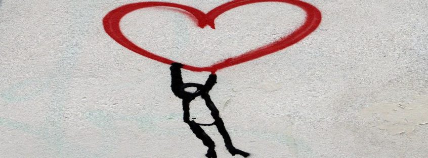 Graffiti showing a person being carried by a heart