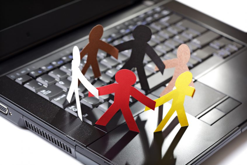 Image of multiple people (paper cutouts) meeting on a computer keyboard