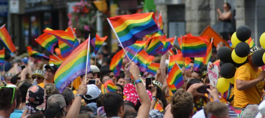 People celebrating and waving flags at Toronto's annual Pride Parade