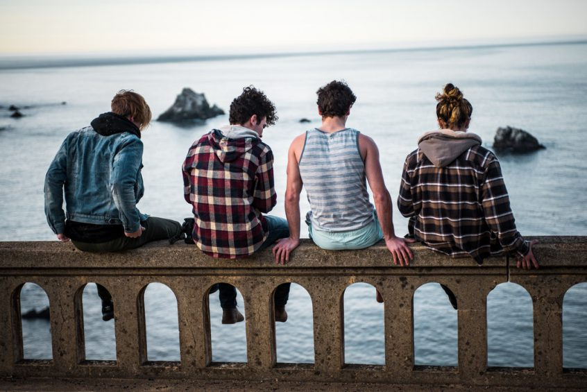 Group of people sitting on barrier overlooking water