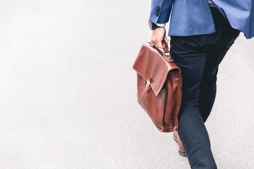 Man wearing business casual attire walking with briefcase on pavement