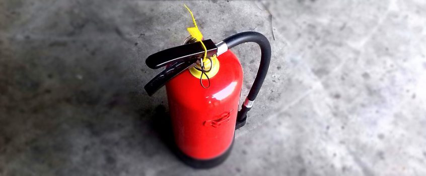 Fire extinguisher sitting on the concrete floor
