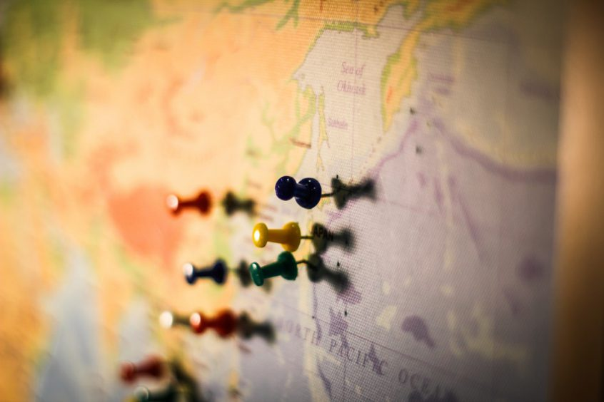 Coloured push pins on world map