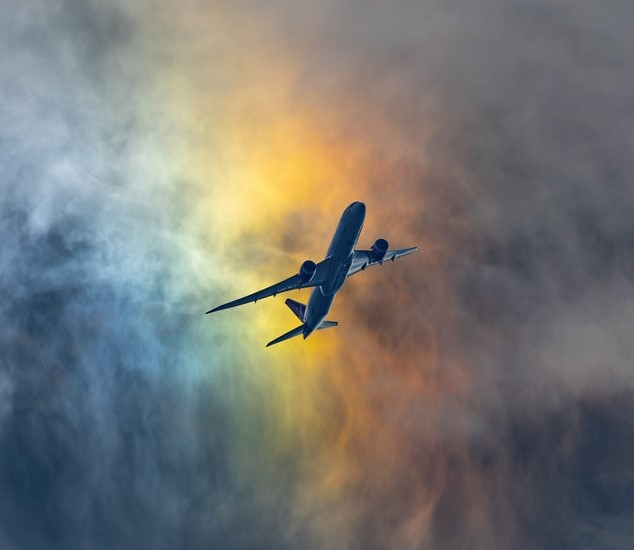 Plane flying in clouds the colour of rainbows.