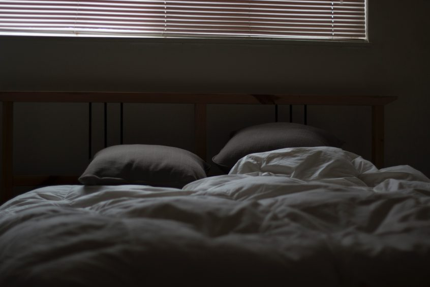 An unmade bed with two pillows