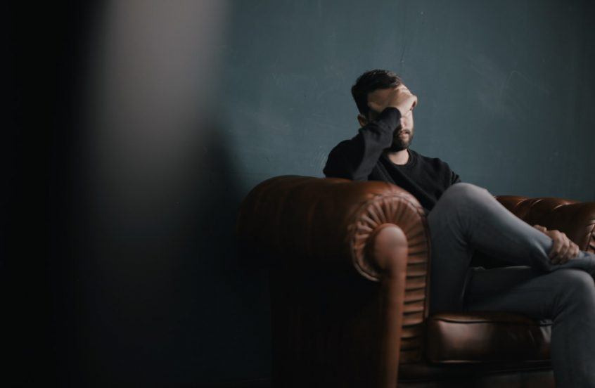 Man sitting on sofa against wall with his right hand covering his eyes and forehead