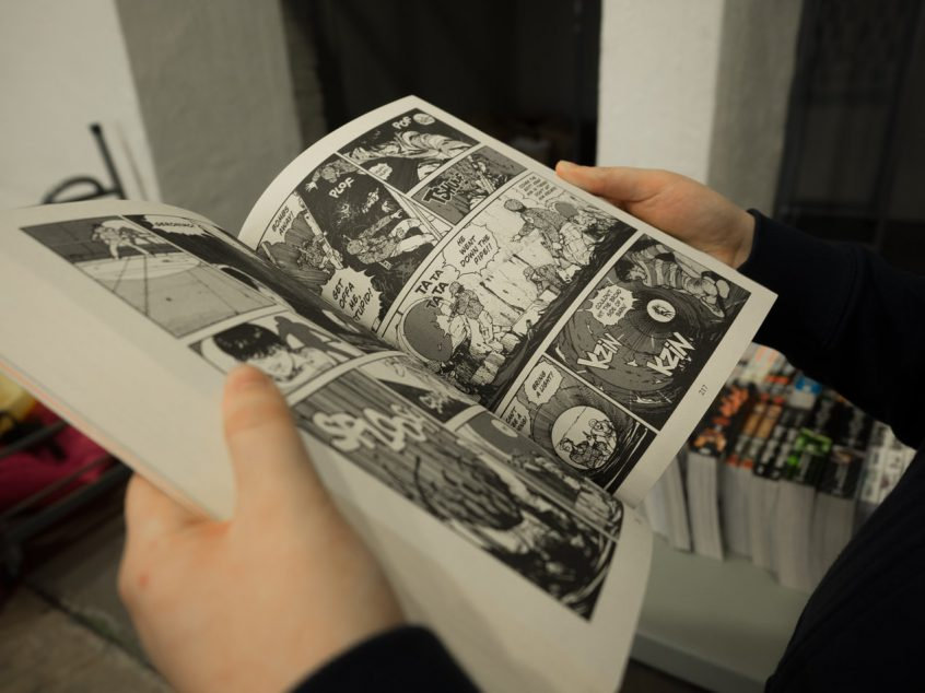 An open comic book being read by a person