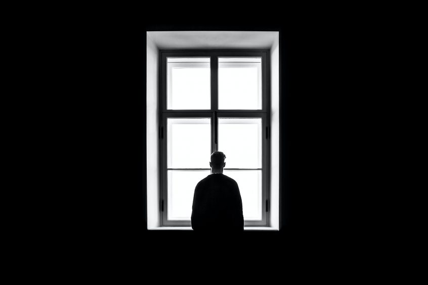 Silhouette of man standing alone face window