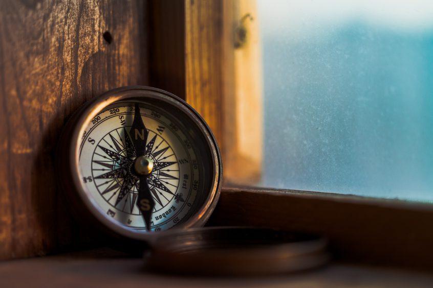 A bronze compass sitting in a windowsill
