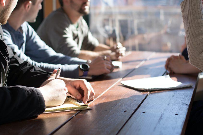 Men sitting around a sunlit table talking