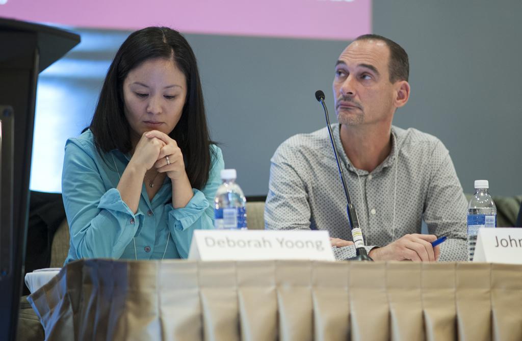 Deborah Yoong and John Maxell listen during a presentation.