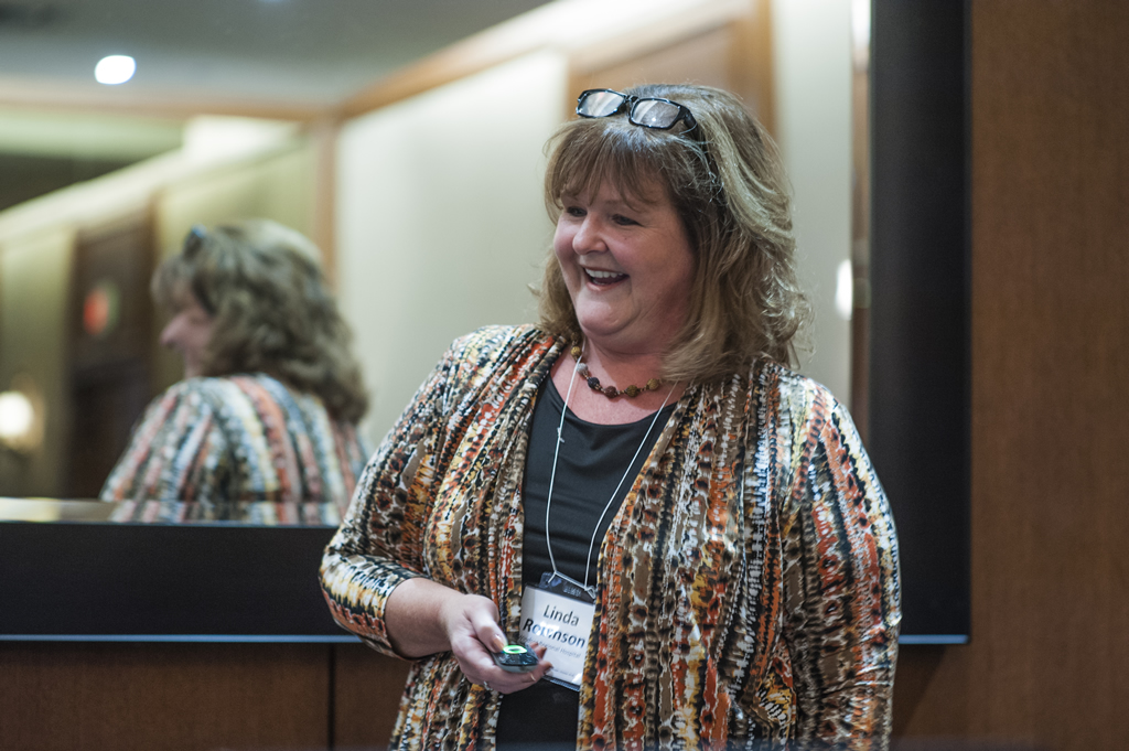 Linda Robinson laughs as she stands to deliver a presentation.