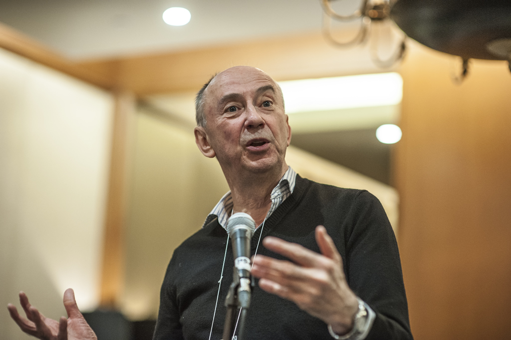 John Gill gestures as he speaks at a microphone.