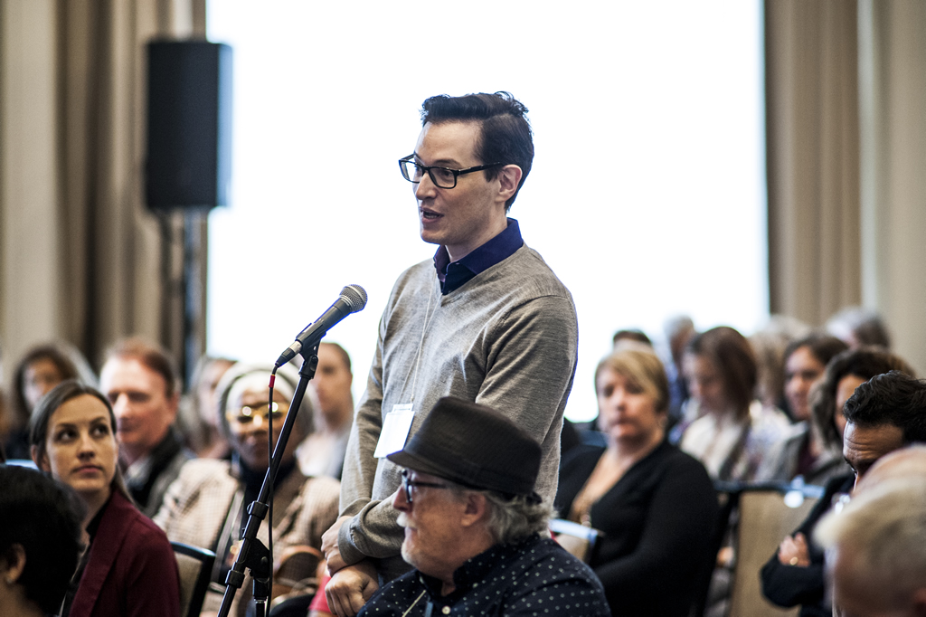An attendee stands at the microphone during a QA.