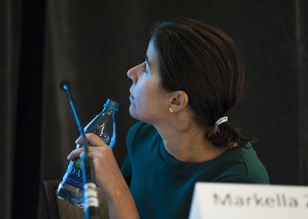 A panelist turns to look at the screen during a presentation.
