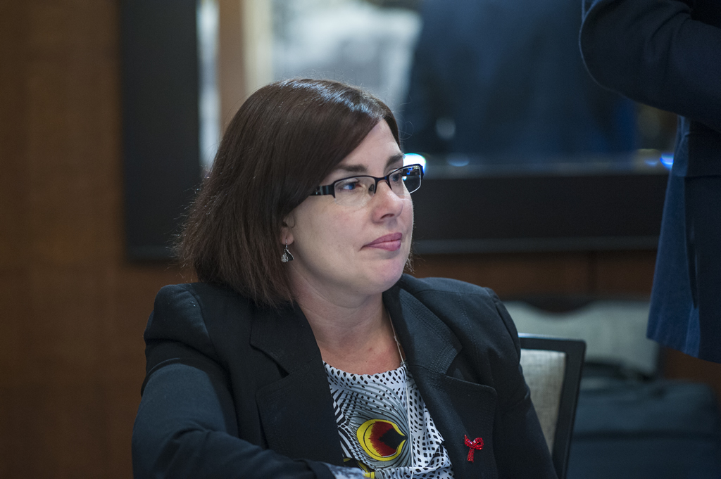 An attendee wearing an AIDS ribbon listens intently during a breakout session.