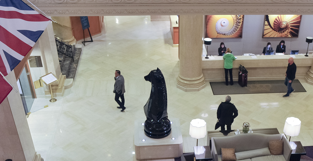 A view of the King Edward hotel lobby shot from the balcony above. The scene is dominated by a large chess knight statue.